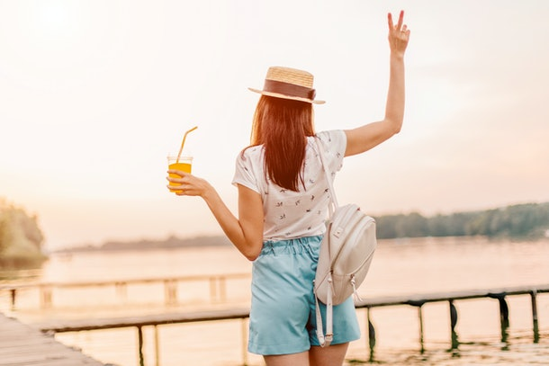 Beautiful young woman walking with orange drink on pier at sunset in summer.