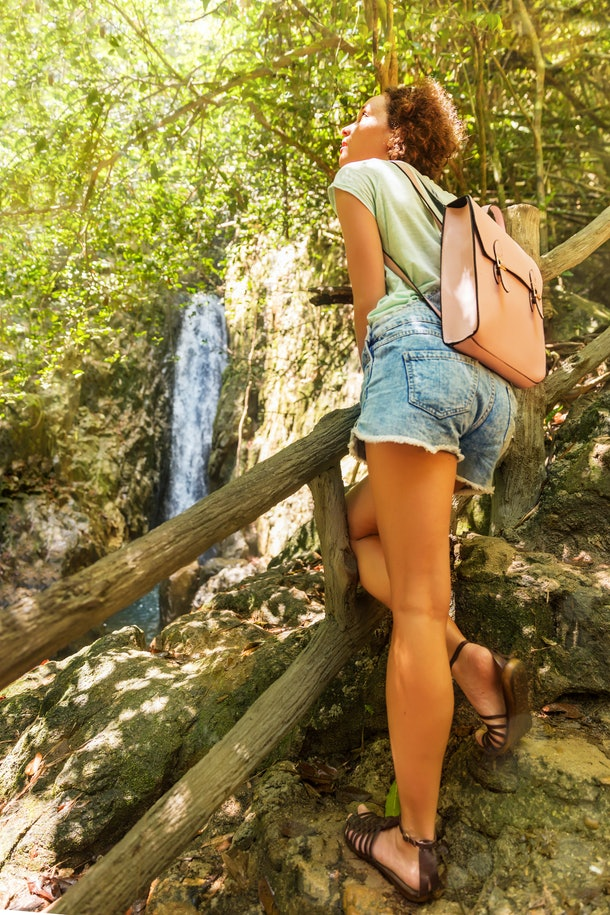 Young woman with hiking bag on a trekking trail to waterfall in tropical rain forest