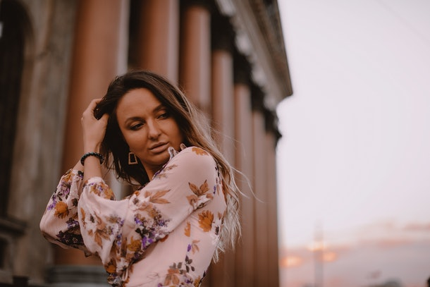 Lovely Woman with Beautiful Eyes, Big Lips and Nude Makeup. Hand on the Head. Brown Ombre Shatush Hair Lying on the Chest. Standing near the Architecture. Wearing Pink Dress. Film Color and Toning