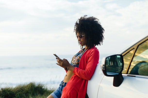 Fashionable afro hair woman on vacation texting on smartphone towards the sea. Stylish black model relaxing on a car trip to the coast.