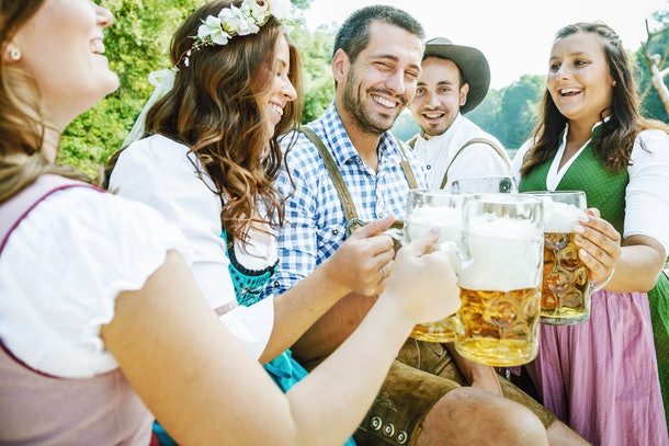 Five friends having fun on Bavarian RIver and clinking glasses with Oktoberfest