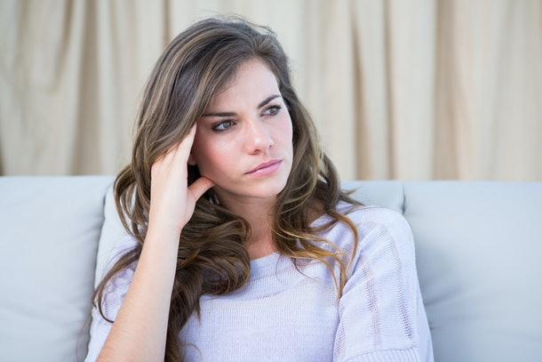 Sad woman looking away at home in the living room