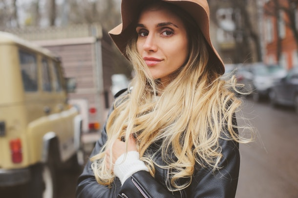 lifestyle portrait of young beautiful woman walking outdoor on city streets, wearing hat and leather jacket. Real people, candid shot.
