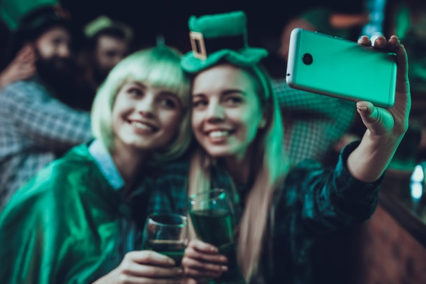 Saint Patrick's Day Party. Friends is Celebrating. Happy People is Drinks a Green Beer. Friends is Young Men and Women. Girls is Doing a Selfie on Cellphone. People Wearing a Green Hats. Pub Interior.