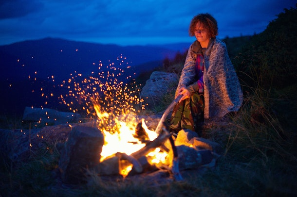 Young caucasian woman near the bonfire at night in the mountains.