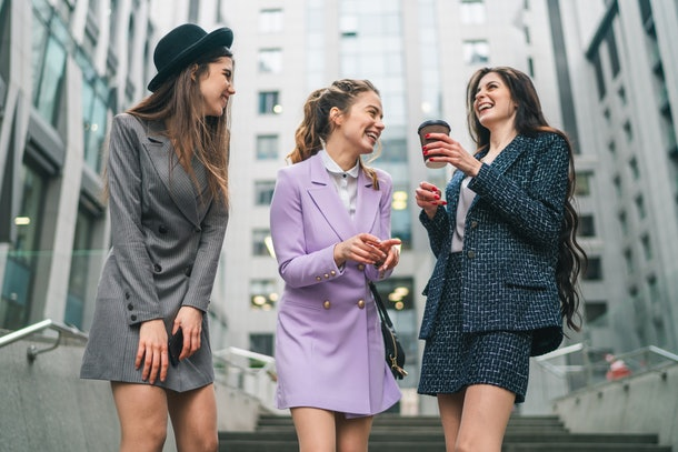 Outdoor shot of three business women in smart trendy outfit having coffee break outside the office center building. Female street fashion.