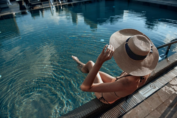 Cropped photo of Caucasian woman wearing sunhat and situating in the swimming pool. Summertime concept