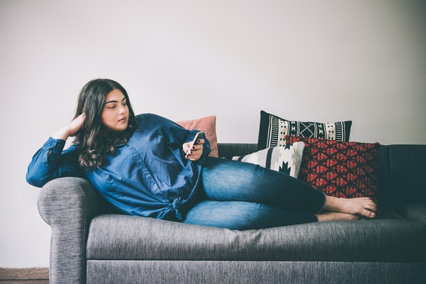 Beautiful plus size girl lying on the sofa with moblile phone. Toned picture