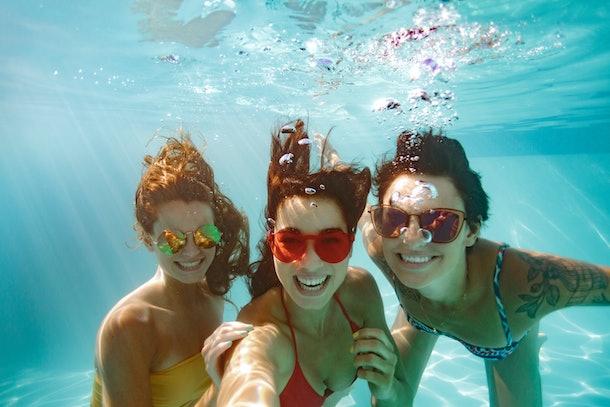 Cheerful women friends swimming underwater in pool taking selfie. Underwater selfie of happy females in pool.