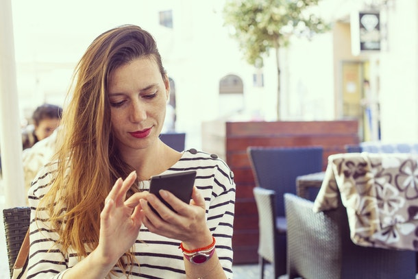 Young lady on bar table using a smart phone, dialing or using some app or sending sms, casual look, black and white striped shirt and light make up, hipster vintage color variation