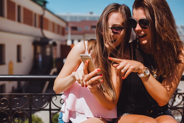 Two friends outside on a balcony with sunglasses on, look at a best friend quiz on a phone.