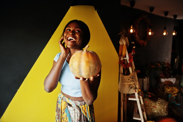 African american girl holding pumpkin against autumn mood decoration. Fall in Africa.