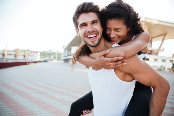 Smiling young man carrying woman on his back and laughing outdoors
