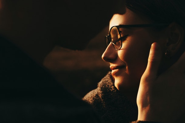 Anonymous guy gently touching face of beautiful female in stylish glasses.Unrecognizable man touching face of girlfriend
