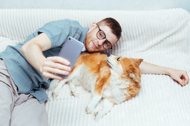 Young guy makes a selfie with a dog on his mobile. Concept blogging