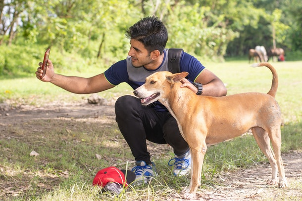 Young sports man taking selfie with dog in park, Animal lover sportsman concept.
