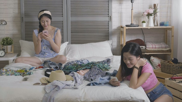 group of young female college student roommates going on vacation adventure trip together packing suitcase on weekends in bedroom. girls resting stop prepare clothes in luggage text on cellphone.