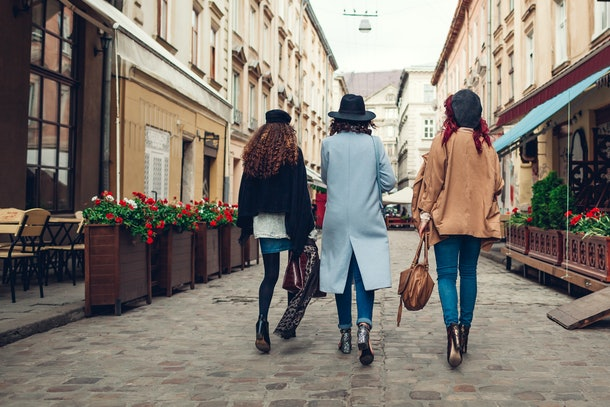Outdoor shot of three young women walking on city street. Girls having fun. Back view