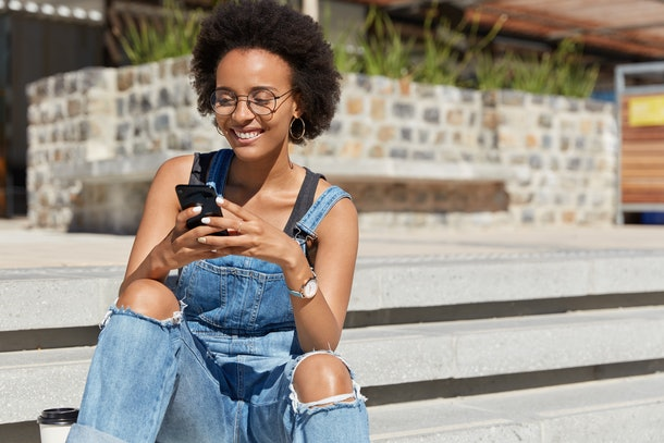 Satisfied blogger texts funny message for post on personal website, dressed in ragged overalls, sends feedback, downloads file, wears eyewear, poses at city steps, copy space for your advertising text