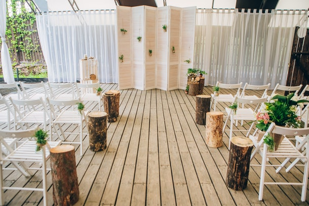 stylish decorated rustic arch with potted flowers. natural style. photo zone. Seating guests. Wedding ceremony.
