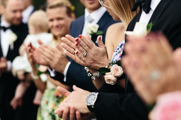 A closeup of the palms of wedding guests while they applaude