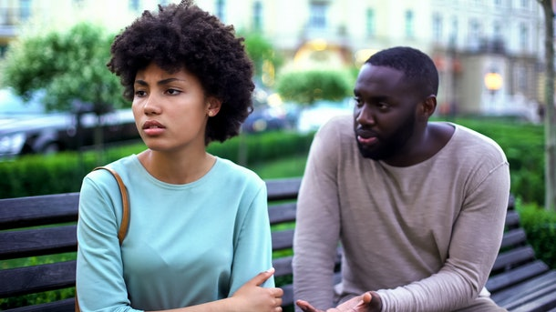 Young man talking to offended girlfriend on bench, jealous woman, break up