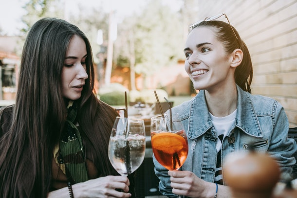 I can tell you everything. Two pretty excited happy young women talking to each other and having dinner cheering with cocktails.