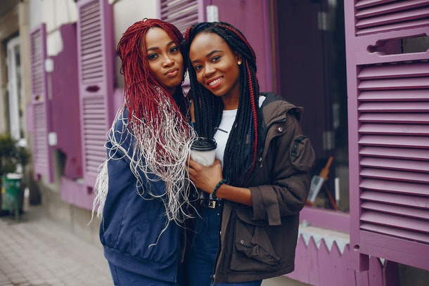 two beautiful and stylish dark-skinned girls with long hair standing in a autumn city near purple wall and drinking a coffee