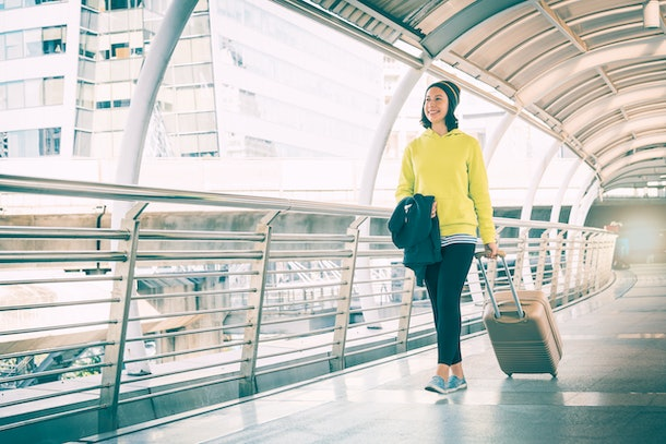 Young traveler woman with luggage walking across sky bridge in the city, Summer holiday vacation and travel trip
