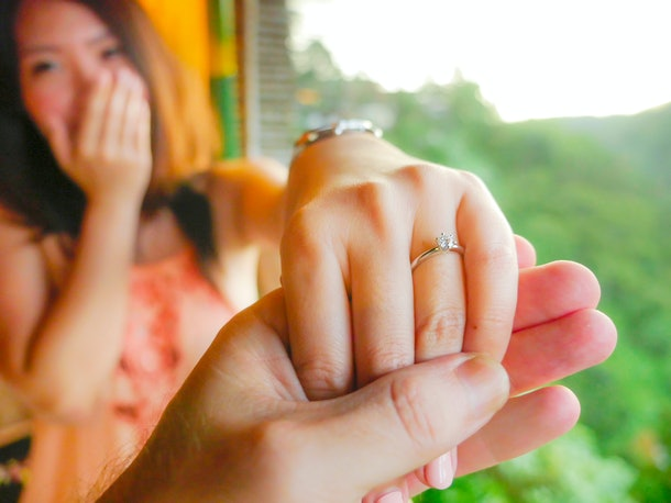 close up couple hands man holding happy fiance hand with diamond engagement ring on her finger after wedding proposal at tropical beautiful and romantic spot proposing marriage