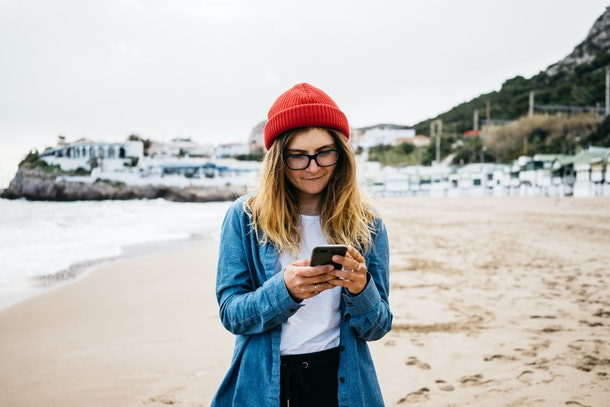 closeup portrait of a stylish female in red beanie smiles while using mobile phone, beach and sea on background. young millennial texts on vacation. women uses mobile app.