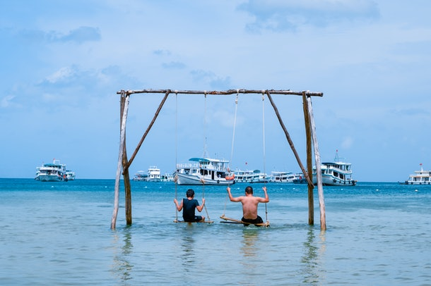 Family, father and son are spending their holidays, swinging on the swing in the sea next to the Bai Sao beach on Phu Quoc island, Vietnam. Sunny day, boats on the background.