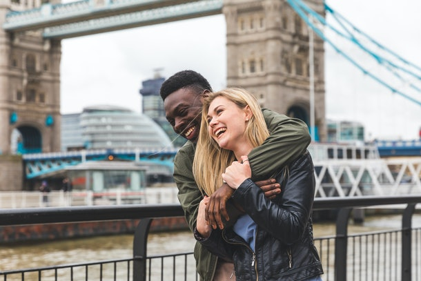 Happy multiracial couple in love in London. Black man and white woman embracing and laughing, bonding and having fun together with Tower Bridge on background. Love and travel concepts