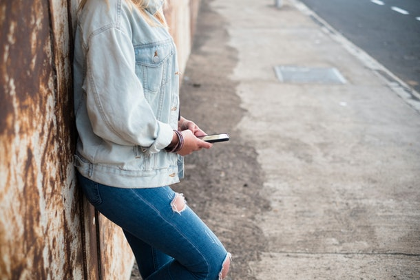 alone girl with phone - girl or teenager with jeans using her smartphone - female holding, playing or working with her mobile