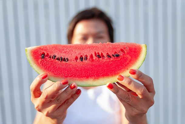 A playful woman holding a watermelon slices with a smile with a happy smile. On a bright day. Is a healthy local fruit