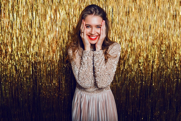 Elegant celebrating woman with surprise  face standing  over  golden sparkling  background. Red lips. New year party.