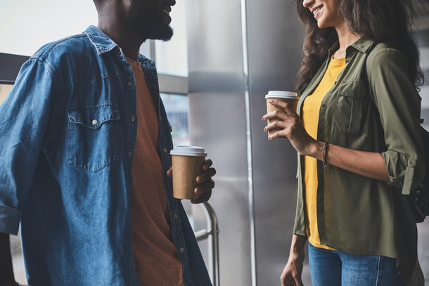 Afro american couple talking and smilling. They are standing in hall near window and holding paper glass with hot drinks