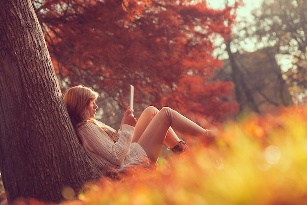 Beautiful young brunette sitting on a fallen autumn leaves in a park, reading an e-book on a tablet computer