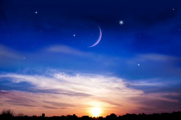 the night sky over the village .  New moon .  Religion background . The sky at night with stars. Ramadan background .