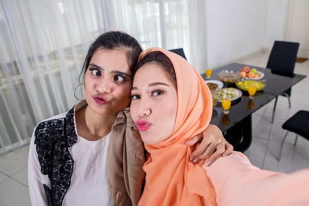 Picture of two Muslim women taking selfie photos with duck face before breaking the fast in the kitchen