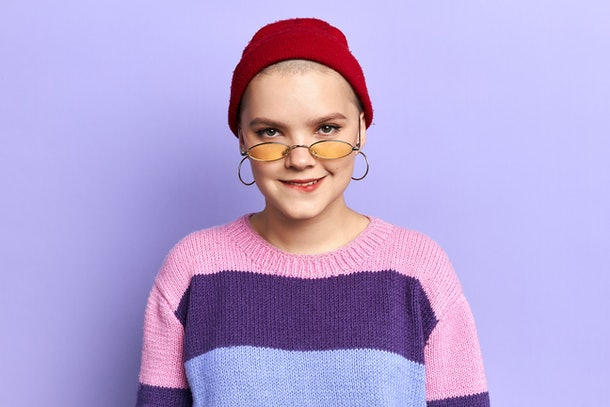 funny cool confused girl in colorful striped fashion sweater biting her lips. close up photo. lifestyle concept