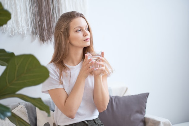 woman drinking water in the morning at home. detox concept, health care. blonde in a white T-shirt in a cozy room.