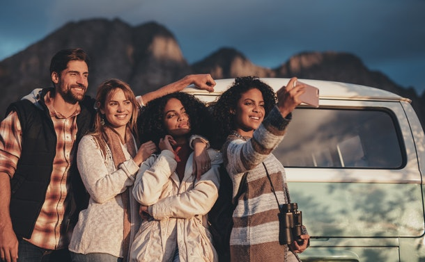 Group of mixed race friends taking a selfie near the van. Young man and women together on road trip making selfie.
