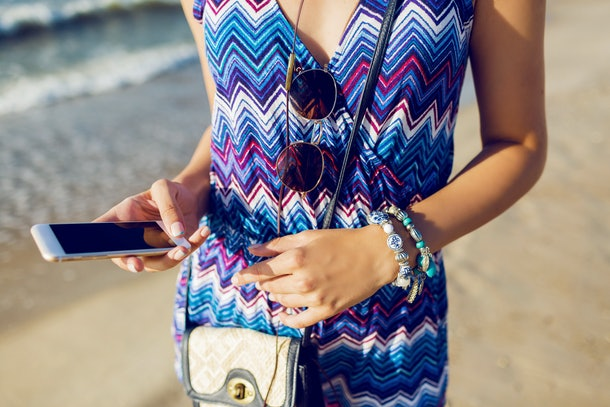 Summer sunny lifestyle image of young woman holding mobile phone, texting message , listening favorite music  . Wearing trendy summer outfit.