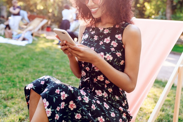 Mixed race girl sitting on chaise-lounge on lawn and  texting message on mobile phone. Summer park on background .  Pretty woman spending her  weekend with friends on nature.