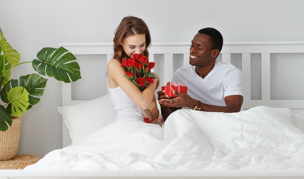 Valentine's Day. happy couple in love with red hert and flowers in bed