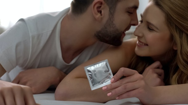 Playful lady giving condom to her boyfriend, lying in bed, safe sex, protection