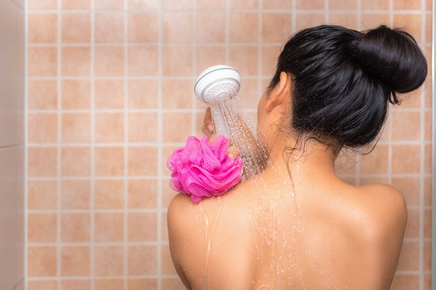 Portrait of beautiful woman taking shower with bath sponge.