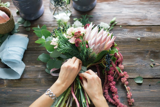 Florist at work: pretty young blond woman making fashion modern bouquet of different flowers