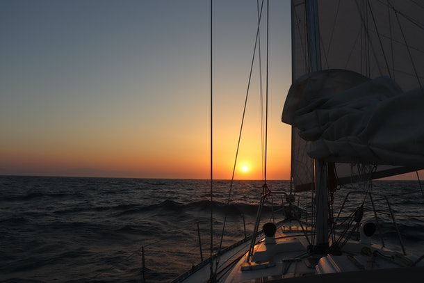 Sailing into the sunset with sailing boat